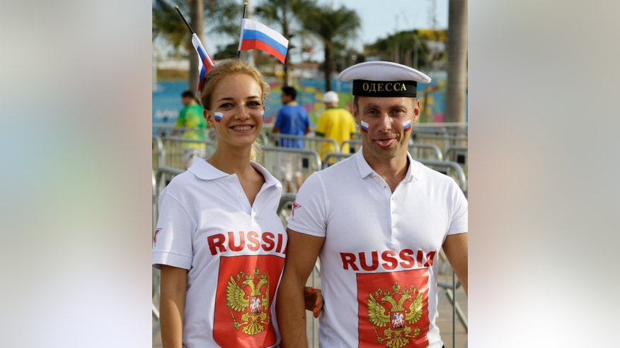 A couple of fans of the Russian national soccer team pose for a picture as they arrive to the Arena Pantanal before the group H World Cup soccer match between Russia and South Korea in Cuiaba, Brazil, Tuesday, June 17, 2014. (AP Photo/Thanassis Stavrakis)