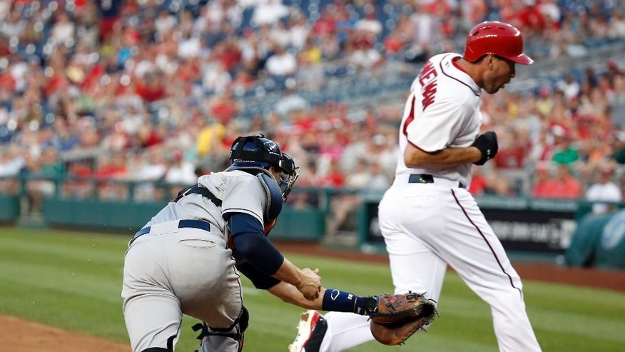 Washington Nationals' Ryan Zimmerman dodges the tag by Houston Astros catcher Jason Castro and is safe at home during the third inning of an interleague baseball game at Nationals Park Tuesday, June 17, 2014, in Washington. (AP Photo/Alex Brandon)