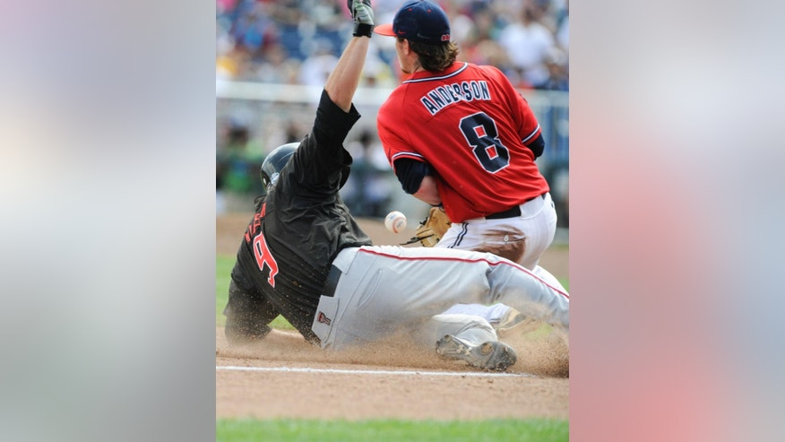 Texas Tech's Alec Humphreys, left, beats the throw to third base against Mississippi third baseman Austin Anderson (8), after Humphreys hit a triple in the sixth inning of an NCAA baseball College World Series elimination game in Omaha, Neb., Tuesday, June 17, 2014. (AP Photo/Eric Francis)