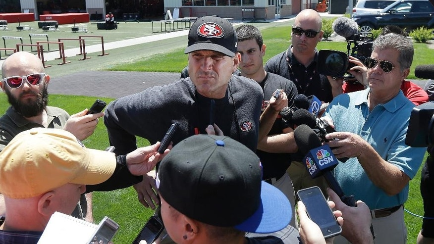 San Francisco 49ers head coach Jim Harbaugh, center, speaks to reporters during NFL football minicamp in Santa Clara, Calif., Tuesday, June 17, 2014. (AP Photo/Jeff Chiu)
