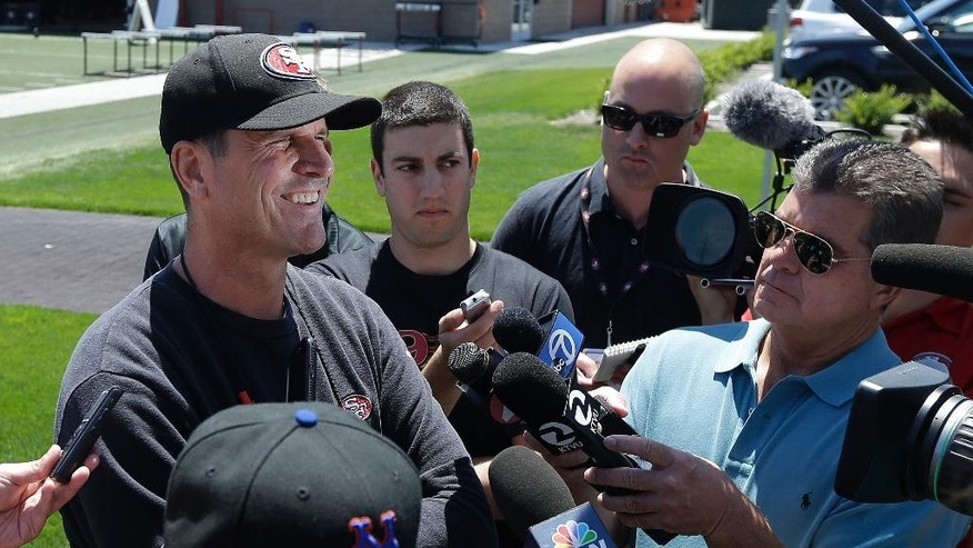 San Francisco 49ers head coach Jim Harbaugh, left, speaks to reporters during NFL football minicamp in Santa Clara, Calif., Tuesday, June 17, 2014. (AP Photo/Jeff Chiu)