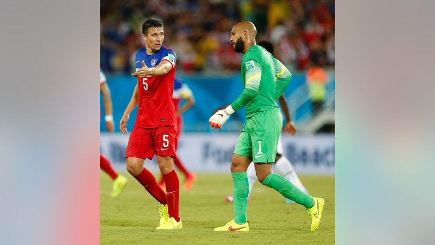 United States' Matt Besler, left, talks to United States' goalkeeper Tim Howard as they walk off the pitch at the half during the group G World Cup soccer match between Ghana and the United States at the Arena das Dunas in Natal, Brazil, Monday, June 16, 2014. (AP Photo/Julio Cortez)