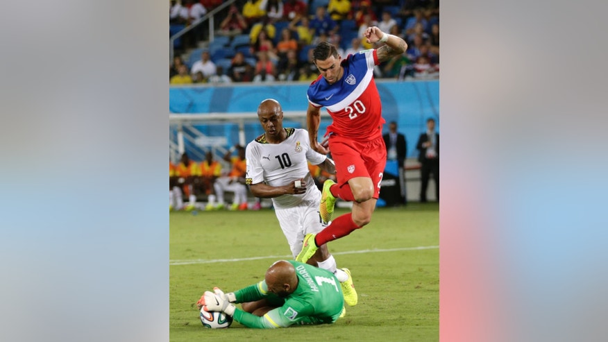 United States' goalkeeper Tim Howard grabs the ball as he makes a save at the feet of his teammate Geoff Cameron, right, and Ghana's Andre Ayew during the group G World Cup soccer match between Ghana and the United States at the Arena das Dunas in Natal, Brazil, Monday, June 16, 2014.  (AP Photo/Dolores Ochoa)