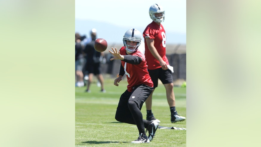 Oakland Raiders rookie quarterback Derek Carr pitches out as quarterback Matt Schaub, right, looks on during the Raiders mini camp in Alameda, Calif., Wednesday, June 18, 2014.  I(AP Photo/Rich Pedroncelli)