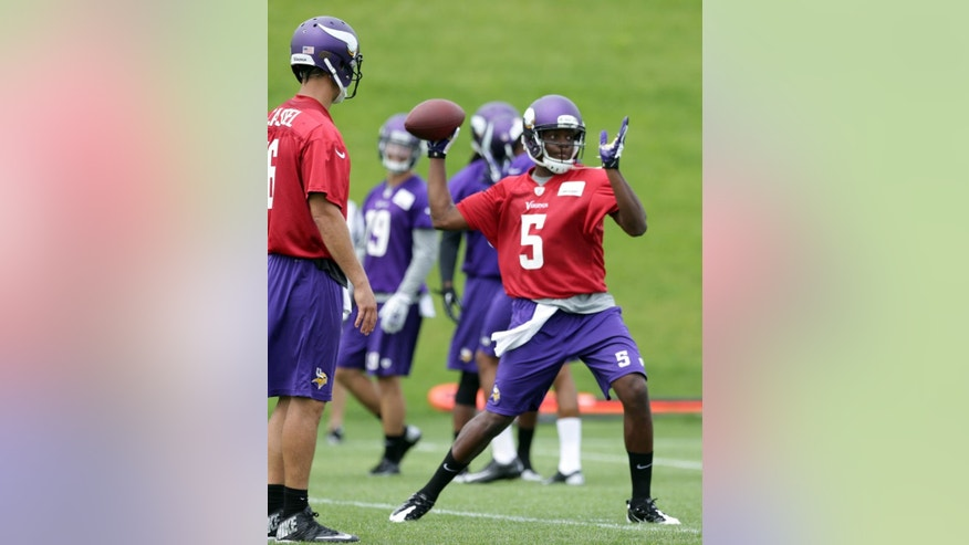Minnesota Vikings quarterback Matt Cassel, left, watches as rookie quarterback Teddy Bridgewater throws during NFL football minicamp Wednesday, June 18, 2014, in Eden Prairie, Minn. (AP Photo/Jim Mone)