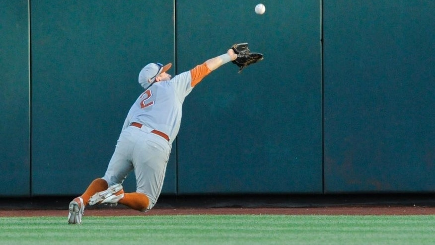 Texas center fielder Mark Payton (2) makes a leaping catch of a fly ball hit by UC Irvine's Taylor Sparks in the third inning of an NCAA baseball College World Series elimination game in Omaha, Neb., Wednesday, June 18, 2014. (AP Photo/Eric Francis)