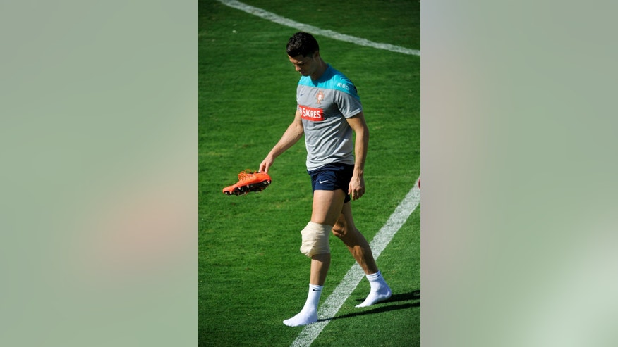 Cristiano Ronaldo leaves the pitch with ice on his left knee after a training session of Portugal in Campinas, Brazil, Wednesday, June 18, 2014. Portugal plays in group G of the Brazil 2014 soccer World Cup. (AP Photo/Paulo Duarte)