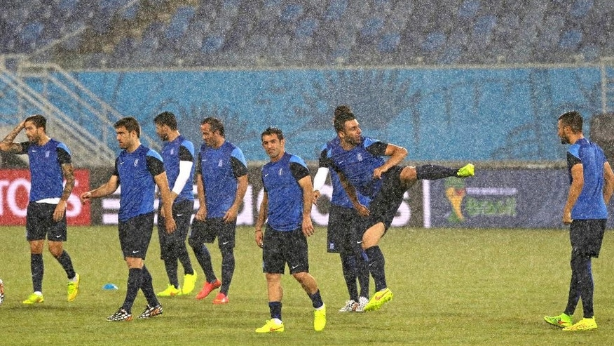 Greece's players walk on the pitch in heavy rain during a training session of Greece at Arena das Dunas in Natal, Brazil, Wednesday, June 18, 2014. Greece play in group C of the 2014 soccer World Cup. (AP Photo/Shuji Kajiyama)