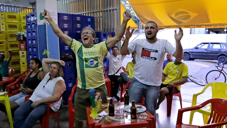 Brazil supporters cheer as they watch on the television the group A World Cup soccer match between Brazil and Mexico, at a bar in Indaiatuba, Brazil, Tuesday, June 17, 2014.(AP Photo/Shuji Kajiyama)