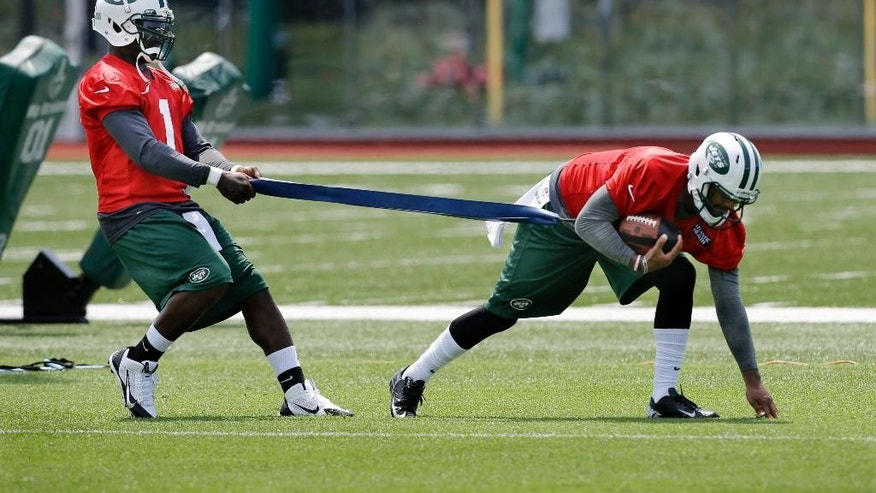 New York Jets quarterback Michael Vick (1) pulls on a stretch-band as fellow quarterback Tajh Boyd (3) runs with the ball during NFL football training minicamp Tuesday, June 17, 2014, in Florham Park, N.J. (AP Photo/Mel Evans)