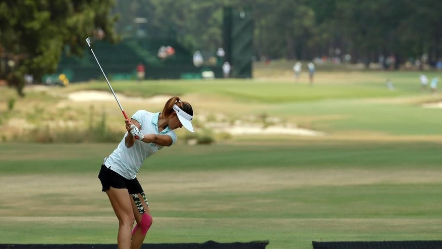 Michelle Wie prepares to hit her tee shot on the first hole during a practice round for the U.S. Women's Open golf tournament in Pinehurst, N.C., Wednesday, June 18, 2014. (AP Photo/Chuck Burton)