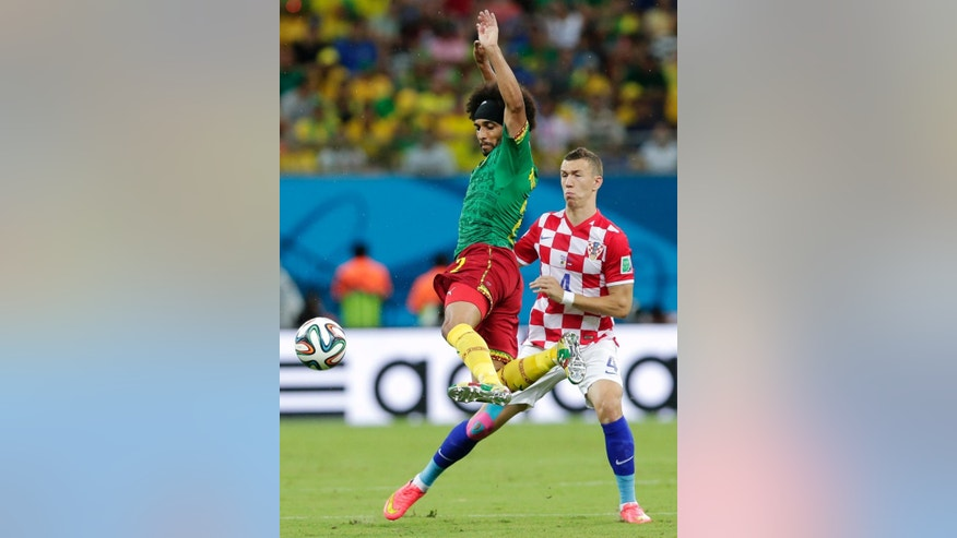 Cameroon's Benoit Assou-Ekotto, left, kicks the ball away from Croatia's Ivan Perisic during the group A World Cup soccer match between Cameroon and Croatia at the Arena da Amazonia in Manaus, Brazil, Wednesday, June 18, 2014.  (AP Photo/Marcio Jose Sanchez)