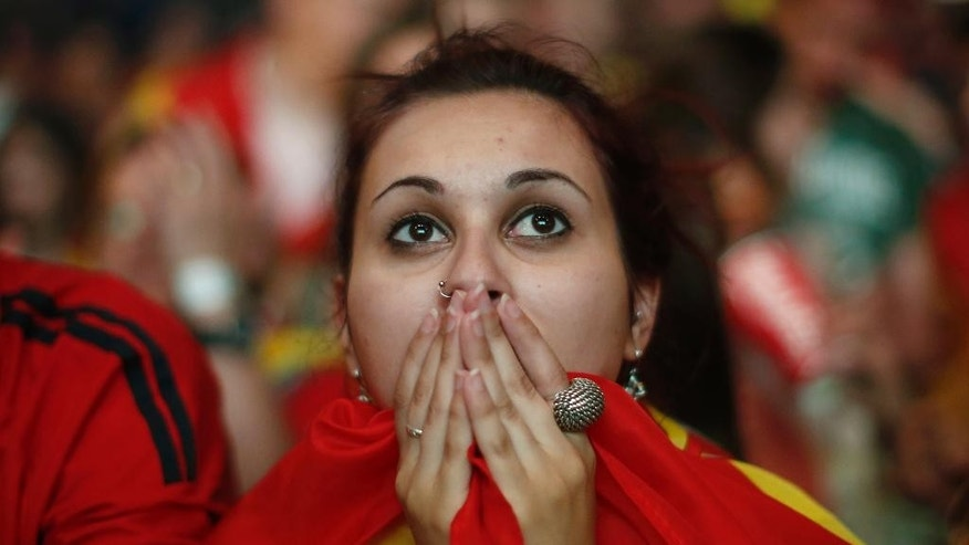 A Spanish soccer fan covers her face as she watches on a giant display a World Cup soccer match between Spain and Chile, in Madrid, Spain, Wednesday, June 18, 2014. (AP Photo/Andres Kudacki)