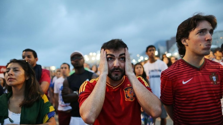 A soccer fan holds his hands to head as he watches the World Cup match between Chile and Spain inside the FIFA Fan Fest area on Copacabana beach, in Rio de Janeiro, Brazil, Wednesday, June 18, 2014. Chile defeated Spain, the defending champs 2-0. (AP Photo/Leo Correa)
