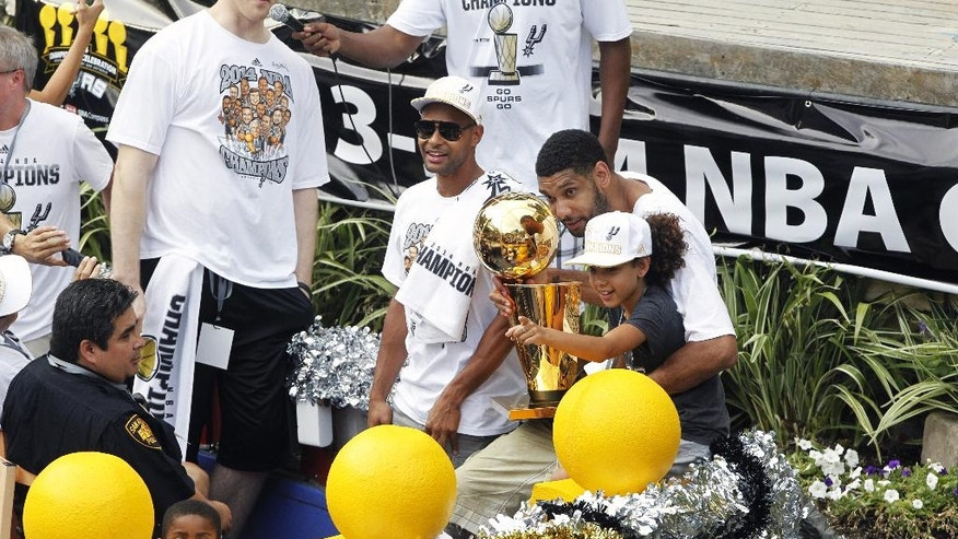 San Antonio's Tim Duncan, right, and his daughter Sidney ride on a float during the team's basektball parade and celebration of their fifth NBA Championship in San Antonio Wednesday, June 18, 2014. (AP Photo/Michael Thomas)