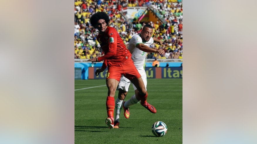 Belgium's Marouane Fellaini, left, and Algeria's Nabil Ghilas battle for the ball during the group H World Cup soccer match between Belgium and Algeria at the Mineirao Stadium in Belo Horizonte, Brazil, Tuesday, June 17, 2014.  (AP Photo/Ricardo Mazalan)