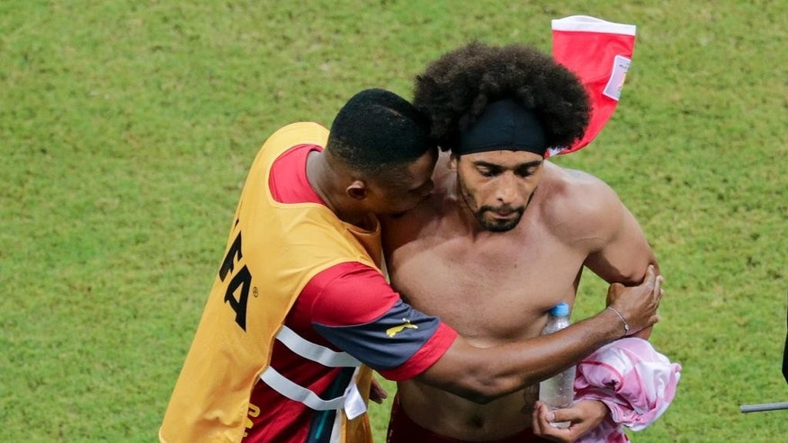 Cameroon's Benoit Assou-Ekotto, right, is comforted after losing 0-4 to Croatia during the group A World Cup soccer match between Cameroon and Croatia at the Arena da Amazonia in Manaus, Brazil, Wednesday, June 18, 2014. (AP Photo/Fernando Llano)