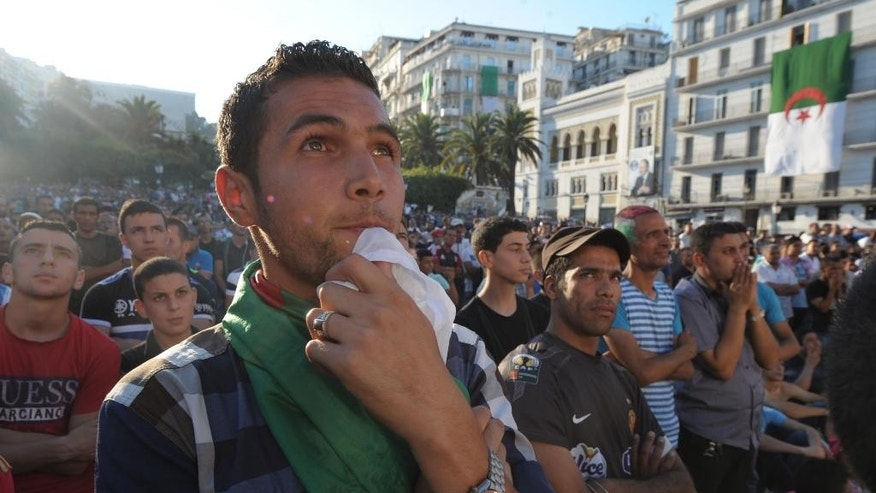 In this photo dated Tuesday, June 17, 2014, Algerian soccer fans watch their team's World Cup soccer match with Belgium on a large screen set up in Algiers Zocalo June 17, 2014. Belgium defeated Algeria 2-1. (AP Photo/Sidali Djarboub)