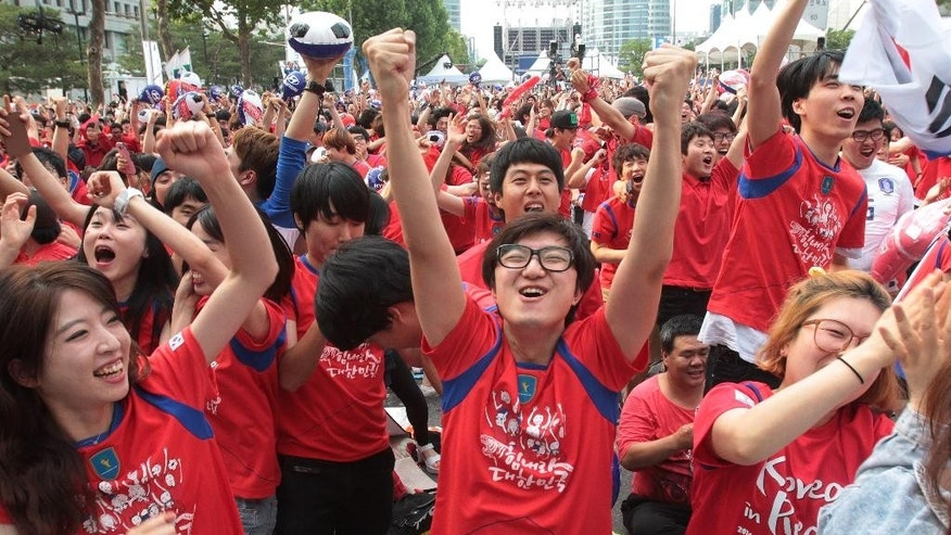 South Korean soccer fans celebrate after their soccer team scored the first goal against  Russia during the group H World Cup soccer match between Russia and South Korea, at a public viewing venue in Seoul, South Korea, Wednesday, June 18, 2014.(AP Photo/Ahn Young-joon)