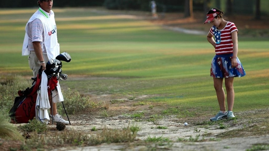 Lucy Li checks out her lie in the waste area on the 11th fairway during the first round of the U.S. Women's Open golf tournament in Pinehurst, N.C., Thursday, June 19, 2014. Looking on is her caddie Bryan Bush. (AP Photo/Chuck Burton)