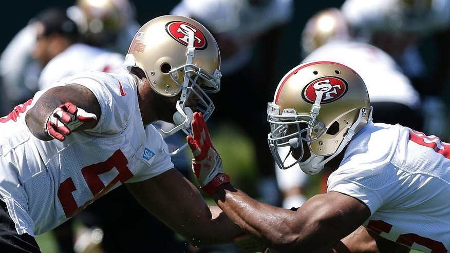 San Francisco 49ers linebackers Ahmad Brooks, left, and Corey Lemonier practice against each other during NFL football mini-camp in Santa Clara, Calif., Wednesday, June 18, 2014. (AP Photo/Jeff Chiu)