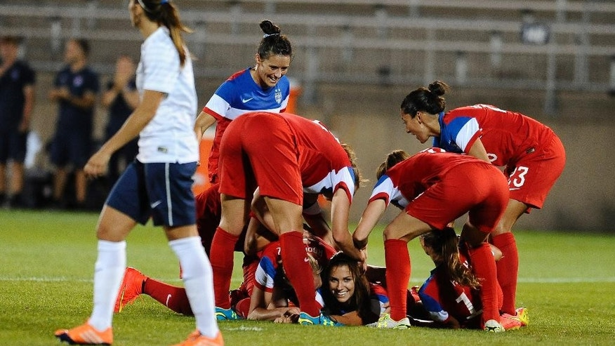United States' Alex Morgan, smiles as her team piles on top of her to celebrate her goal during the second half of a women's friendly soccer match against France, Thursday, June 19, 2014, in East Hartford, Conn. The final score was 2-2. (AP Photo/Jessica Hill)