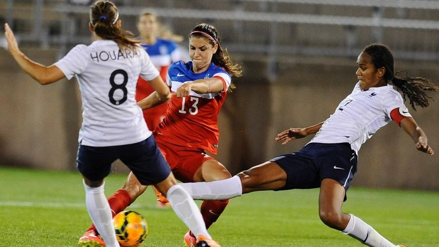 United States' Alex Morgan, center, kicks a goal as France's Jessica Houara, left, and Wendie Renard, right, defend, during the second half of a women's friendly soccer match on Thursday, June 19, 2014, in East Hartford, Conn.  The final score was 2-2. (AP Photo/Jessica Hill)