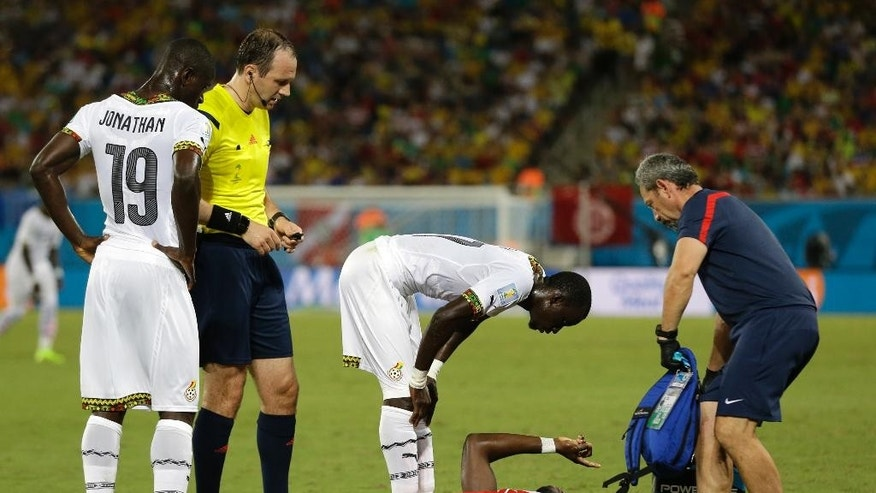 United States' Jozy Altidore gestures as he lies on the pitch after pulling up injured, as referee Jonas Eriksson of Sweden, looks on as a United States team trainer arrives to help during the group G World Cup soccer match between Ghana and the United States at the Arena das Dunas in Natal, Brazil, Monday, June 16, 2014. (AP Photo/Ricardo Mazalan)