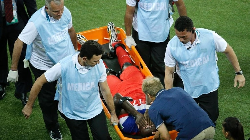 United States' Jozy Altidore is attended to by head coach Juergen Klinsmann, bottom, as he is carried off the pitch during the group G World Cup soccer match between Ghana and the United States at the Arena das Dunas in Natal, Brazil, Monday, June 16, 2014. (AP Photo/Hassan Ammar)