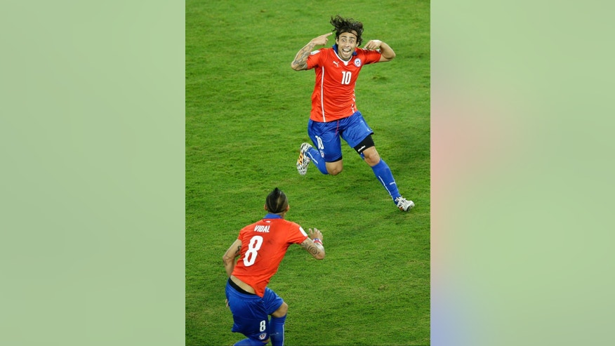 In this Friday, June 13, 2014 photo, Chile's Jorge Valdivia, top, celebrates after scoring his side's second goal during the group B World Cup soccer match between Chile and Australia in the Arena Pantanal in Cuiaba, Brazil. Chile went on to defeat Australia 3-1. (AP Photo/Michael Sohn)