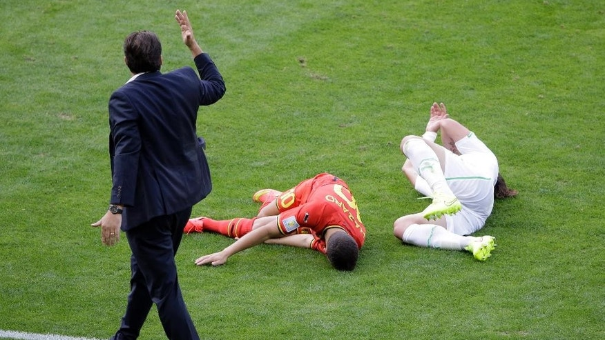Belgium's head coach Marc Wilmots gestures to referee after Belgium's Eden Hazard collided with Algeria's Mehdi Mostefa, right, during the group H World Cup soccer match between Belgium and Algeria at the Mineirao Stadium in Belo Horizonte, Brazil, Tuesday, June 17, 2014.  (AP Photo/Sergei Grits)