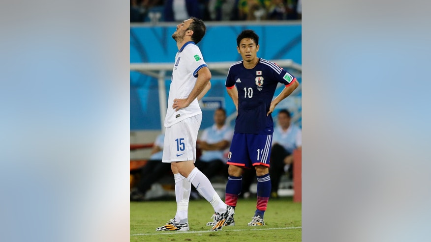 Greece's Vasilis Torosidis, left, and Japan's Shinji Kagawa stand on the pitch following their 0-0 tie with Greece during the group C World Cup soccer match between Japan and Greece at the Arena das Dunas in Natal, Brazil, Thursday, June 19, 2014.  (AP Photo/Shuji Kajiyama)