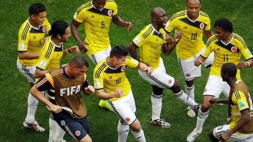 Colombia's James Rodriguez, center, dances with teammates in celebration after scoring during the group C World Cup soccer match between Colombia and Ivory Coast at the Estadio Nacional in Brasilia, Brazil, Thursday, June 19, 2014.  (AP Photo/Themba Hadebe)