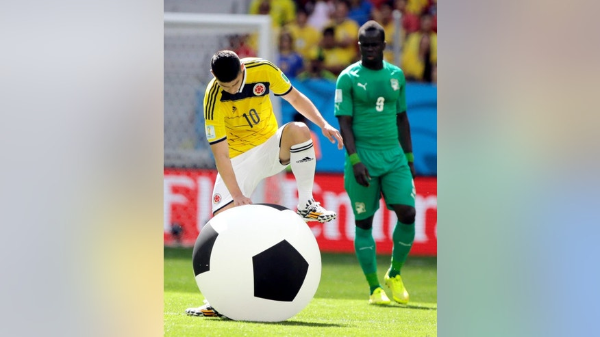 Colombia's James Rodriguez deflates a large inflatable ball that was thrown onto the pitch during the group C World Cup soccer match between Colombia and Ivory Coast at the Estadio Nacional in Brasilia, Brazil, Thursday, June 19, 2014.  (AP Photo/Marcio Jose Sanchez)