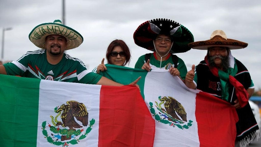 The Trejo family from Los Angeles poses outside of the Arena Castelao before the group A World Cup soccer match between Brazil and Mexico in Fortaleza, Brazil, Tuesday, June 17, 2014. A great number of fans that have come to Brazil to cheer for Mexico do not come from Mexico but rather from cities in the U.S. and entering Brazil with American passports. (AP Photo/Eduardo Verdugo)