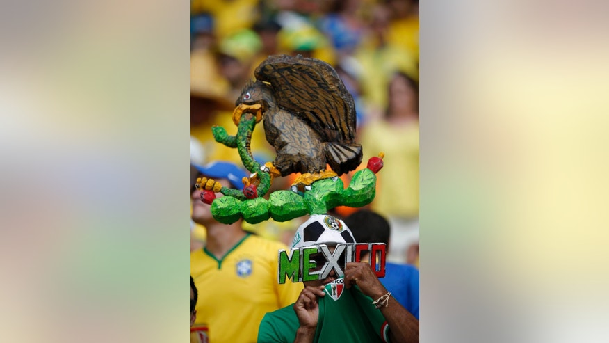A Mexican fan kisses the team emblem on his shirt before the group A World Cup soccer match between Brazil and Mexico at the Arena Castelao in Fortaleza, Brazil, Tuesday, June 17, 2014.  The number of fans cheering Mexico at the World Cup has taken observers in Brazil by surprise. But talk to those waving the green-white-and-red, and it becomes clear that when the tournament ends, many will return home not to Mexico, but to the United States. (AP Photo/Eduardo Verdugo)