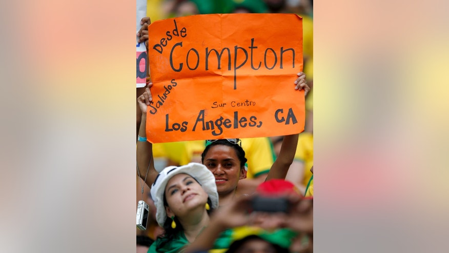 A Mexican fan holds up a sign saying he comes from Compton in southern Los Angeles County, before the group A World Cup soccer match between Brazil and Mexico at the Arena Castelao in Fortaleza, Brazil, Tuesday, June 17, 2014. The number of fans cheering Mexico at the World Cup has taken observers in Brazil by surprise. But talk to those waving the green-white-and-red, and it becomes clear that when the tournament ends, many will return home not to Mexico, but to the United States. (AP Photo/Eduardo Verdugo)