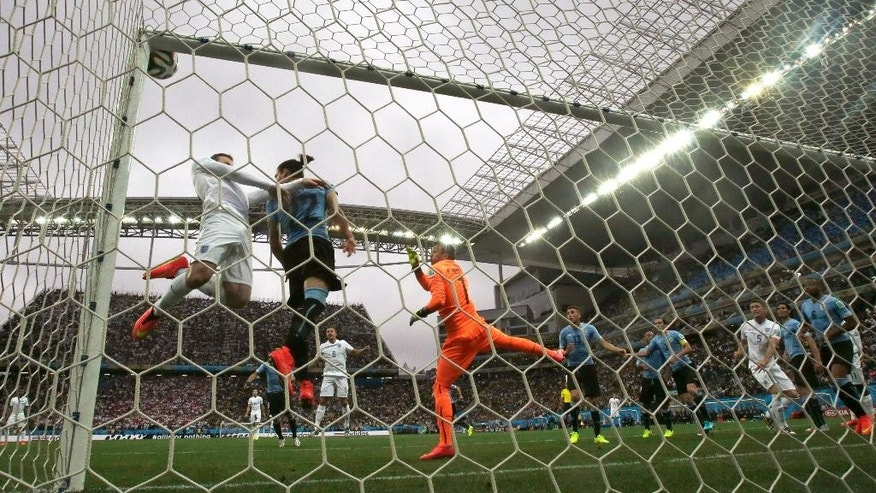 England's Wayne Rooney, left, in white, heads the ball at the crossbar as Uruguay's goalkeeper Fernando Muslera, right in orange, watches during the group D World Cup soccer match between Uruguay and England at the Itaquerao Stadium in Sao Paulo, Brazil, Thursday, June 19, 2014.  (AP Photo/Thanassis Stavrakis)