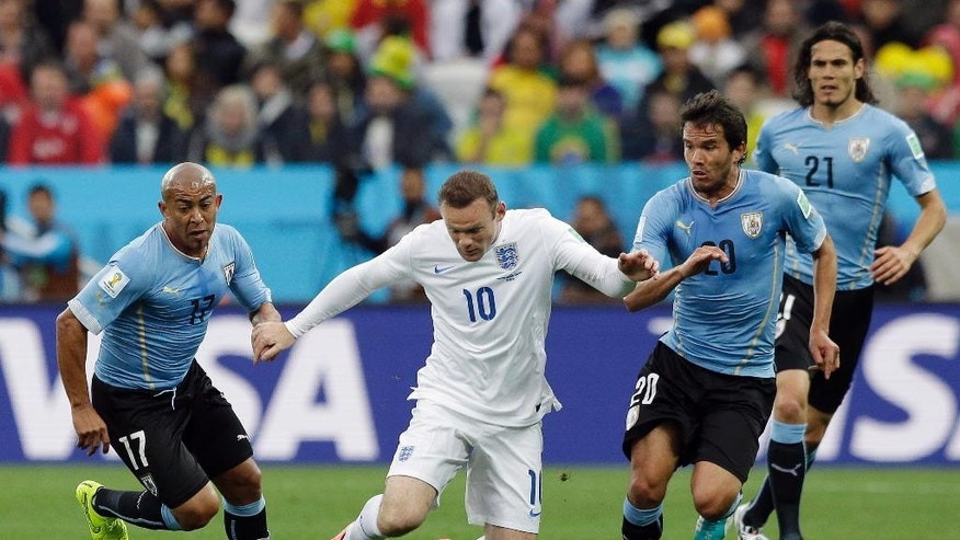 England's Wayne Rooney, second left, takes on the Uruguay defense during the group D World Cup soccer match between Uruguay and England at the Itaquerao Stadium in Sao Paulo, Brazil, Thursday, June 19, 2014.  (AP Photo/Matt Dunham)