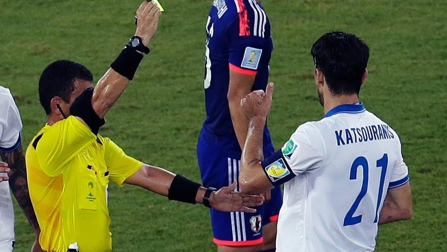 Greece's Kostas Katsouranis is booked by referee Joel Aguilar from El Salvador during the group C World Cup soccer match between Japan and Greece at the Arena das Dunas in Natal, Brazil, Thursday, June 19, 2014. (AP Photo/Hassan Ammar)