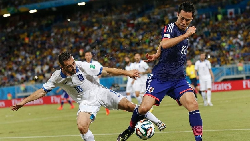 Greece's Giannis Fetfatzidis, left, challenges Japan's Maya Yoshida during the group C World Cup soccer match between Japan and Greece at the Arena das Dunas in Natal, Brazil, Thursday, June 19, 2014. (AP Photo/Frank Augstein)