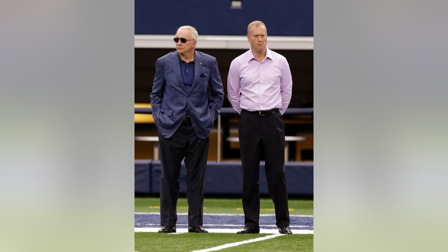Dallas Cowboys owner Jerry Jones, left, stands on the sidelines with his son  Jerry Jones, Jr. during NFL football minicamp at the team's stadium Thursday, June 19, 2014, in Arlington, Texas. Jones says he expects the defense to be better even without Sean Lee, because there's no way that unit could be any worse than it was in 2013. He also says it's too early to think about Josh Brent's return to football once he is released in an intoxication manslaughter case. (AP Photo/LM Otero)