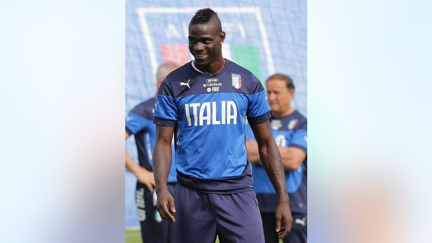 Italy's Mario Balotelli smiles during a training session in Mangaratiba, Brazil, Wednesday, June 18, 2014. Italy plays in group D at the 2014 soccer World Cup. (AP Photo/Antonio Calanni)