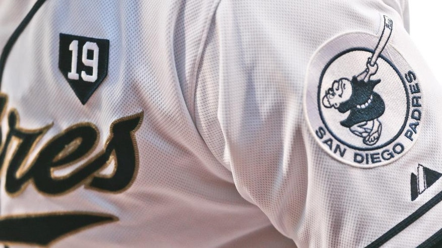 The number 19 center in a home plate design is worn on the chest of all San Diego Padres in honor of Hall of Fame player Tony Gwynn during a baseball game against the Seattle Mariners Wednesday, June 18, 2014, in San Diego.  Gwynn died Monday from cancer. (AP Photo/Lenny Ignelzi)