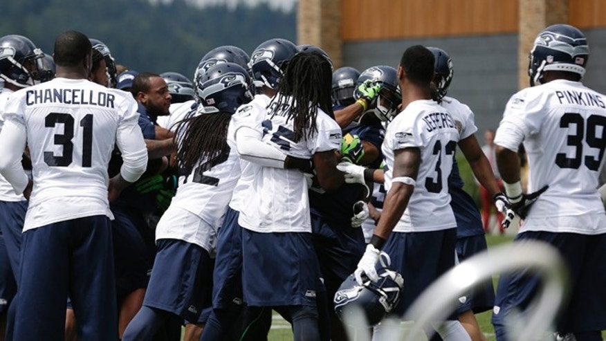 June 18, 2014: Seattle Seahawks players continue to scuffle as Richard Sherman, center, is pulled back at an NFL football minicamp practice in Renton, Wash. (AP)