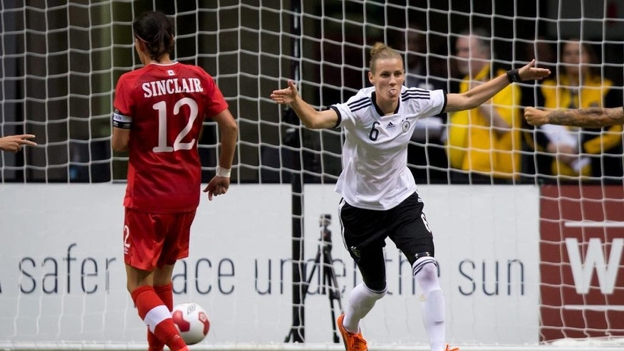 Germany's Simone Laudehr, right, celebrates her penalty kick goal as Canada's Christine Sinclair looks on during the second half of an international women's soccer game in Vancouver, British Columbia on Wednesday, June 18, 2014.  (AP Photo/The Canadian Press, Darryl Dyck)