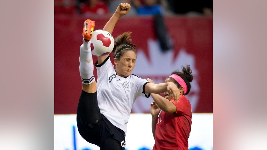 Germany's Nadine Kebler, left, tries to get her foot on the ball but misses while under pressure from Canada's Desiree Scott during the second half of an international women's soccer game in Vancouver, British Columbia on Wednesday, June 18, 2014.  (AP Photo/The Canadian Press, Darryl Dyck)