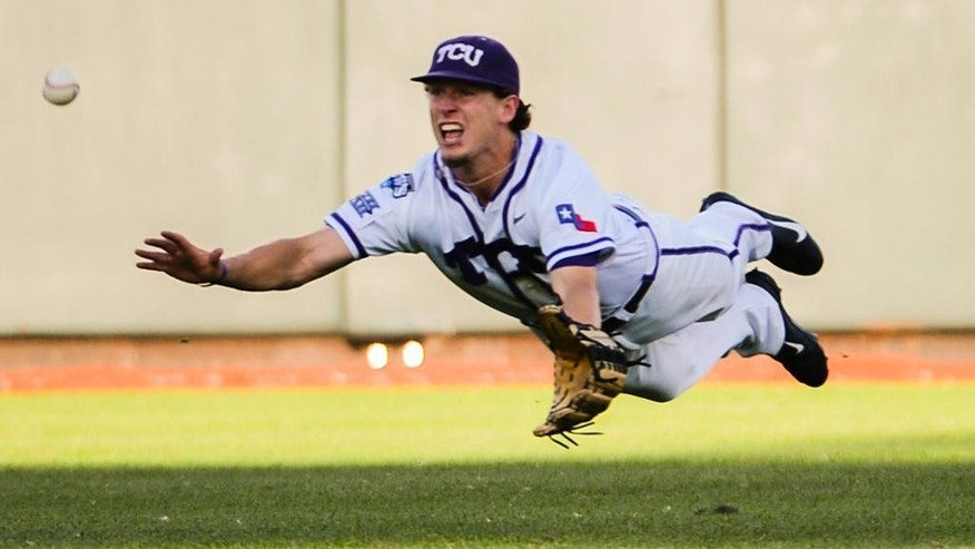 TCU Center fielder Cody Jones dives for and misses a ball hit for a double by Mississippi's J.B. Woodman in the third inning of an NCAA baseball College World Series elimination game in Omaha, Neb., Thursday, June 19, 2014. (AP Photo/Ted Kirk)