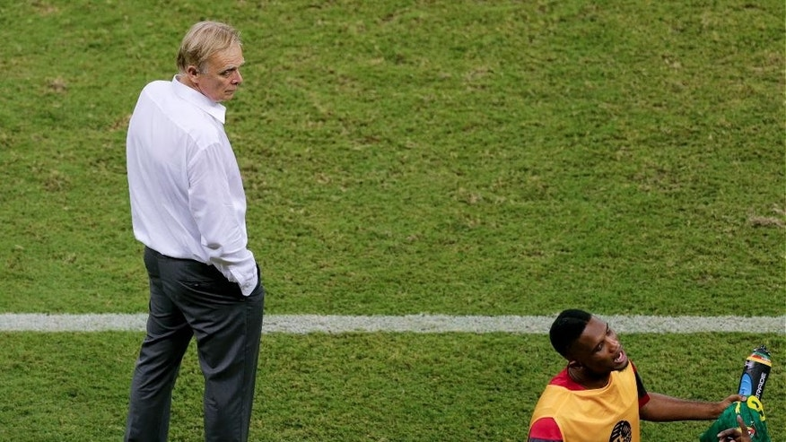 Cameroon's coach Volker Finke, left, looks to arguing players during the group A World Cup soccer match between Cameroon and Croatia at the Arena da Amazonia in Manaus, Brazil, Wednesday, June 18, 2014. (AP Photo/Fernando Llano)