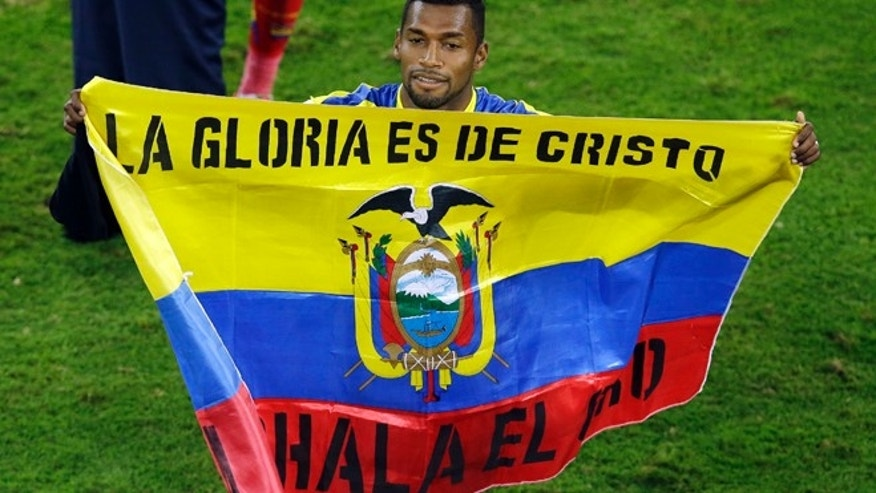 June 20, 2014: Ecuador's Gabriel Achilier holds a Ecudorian flag with the writing 'The glory is for Christ' after winning 2-1 during the group E World Cup soccer match between Honduras and Ecuador at the Arena da Baixada in Curitiba, Brazil.